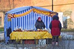 普斯克夫,俄罗斯, 2017年12月, 31日 在周末市场上的妇女在普希金街道上在普斯克夫 亭子`斯摩棱斯克产品` 免版税库存图片