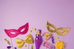 普珥节与狂欢节面具和党供应的假日概念在紫色背景 顶视图从上面 免版税图库摄影