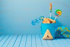 普珥节传统礼物与hamantaschen曲奇饼、发出大声音的人和狂欢节面具 免版税库存图片