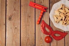 普珥节假日与小丑面具的概念庆祝和hamantaschen在木背景的曲奇饼 图库摄影
