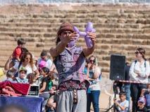 普珥节节日的参加者在凯瑟里雅,以色列显示与一个可膨胀的球的表现访客的 免版税库存图片
