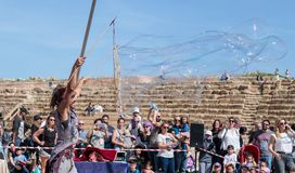 普珥节节日的参加者在凯瑟里雅,以色列显示与肥皂泡的一个展示访客的 免版税库存图片