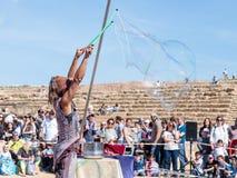 普珥节节日的参加者在凯瑟里雅,以色列显示与肥皂泡的一个展示访客的 免版税库存照片