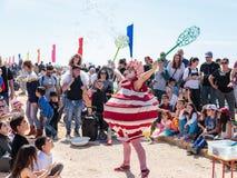 普珥节节日的参加者在美妙的服装穿戴了,在凯瑟里雅,以色列显示与肥皂泡的一个展示 免版税库存图片