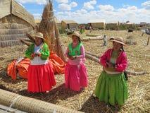 普诺,秘鲁-大约2015年6月:唱歌在Uros浮动海岛和村庄的妇女的喀喀湖的在普诺,秘鲁附近 库存照片
