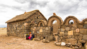 普诺,秘鲁- 2011年12月10日:在小农场前面的孩子在Sillustani附近坟茔在普诺,玻利维亚附近的 免版税图库摄影