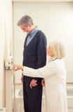 普通开业医生测量的男性患者的高度在医院 免版税图库摄影