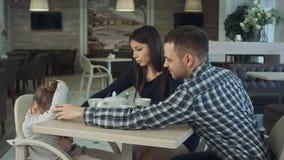 普通的三口之家与咖啡馆的小女儿 再保证他们的孩子的父母 免版税库存照片