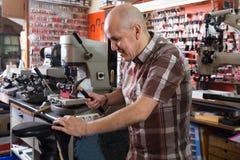 普通的在针车床的工作员缝合的皮靴 库存照片