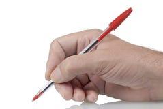 普通的红色圆珠笔在男性手上 免版税库存图片