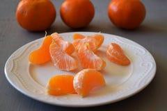 普通话、被剥皮的蜜桔和蜜桔切片在一张木桌上 免版税图库摄影
