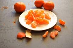 普通话、被剥皮的蜜桔和蜜桔切片在一张木桌上 免版税库存照片