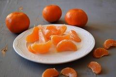 普通话、被剥皮的蜜桔和蜜桔切片在一张木桌上 库存图片