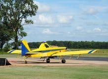 普通黄色和蓝色庄稼喷粉器飞机 免版税库存照片