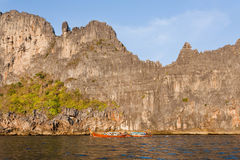普遍的潜水的点在安达曼海 岩石峭壁和一条渔夫小船在蓝天下 库存照片