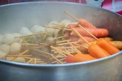 普遍的街道食物肉丸、猪肉球、鱼丸和香肠用竹棍子在通入蒸汽的罐待售在摊位在fr 库存照片