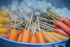 普遍的街道食物肉丸、猪肉球、鱼丸和香肠用竹棍子在通入蒸汽的罐待售在摊位在fr 免版税库存照片