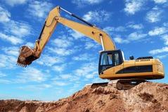 景气被上升的挖掘机装入程序 库存图片
