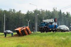 景气起重机为举一辆被弄翻的卡车到达了,莫斯科郊区,俄罗斯 库存照片