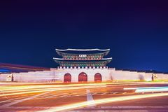 景福宫宫殿著名Gwanghwamun门在汉城,有汽车尾灯和车灯的韩国在它前面的 图库摄影