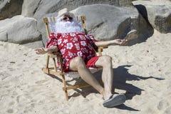 晴朗的海滩的圣诞老人 库存照片