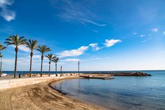 晴朗的海滩,有棕榈树的散步在托雷维耶哈,西班牙 免版税库存照片