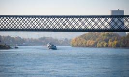 晴朗的秋天天在河的莱茵河德国 驳船流动在铁路桥下 核能pla的一个可看见的烟囱 库存照片