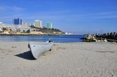 晴朗被放弃的海滩的小船 免版税库存照片