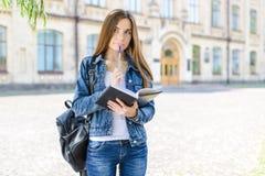 !智力人生活方式牛仔裤概念 关闭拿着penc的逗人喜爱的美丽的可爱的聪明的聪明的女孩照片画象  免版税库存照片