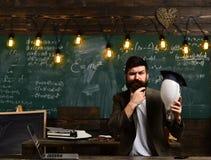 智力任务概念 有电灯泡的有胡子的在背景的行家和黑板 认为与周道的人 库存照片