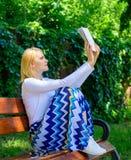 智力爱好 女孩坐放松与书,绿色自然背景的长凳 夫人俏丽的书痴繁忙的读的书 库存照片
