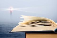 智慧概念-在海和灯塔背景的开放书 免版税库存图片