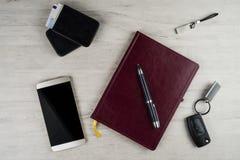 智能手机、书桌垫、点火开关、笔和其他人` s辅助部件表面上与被漂白的橡木纹理  免版税图库摄影