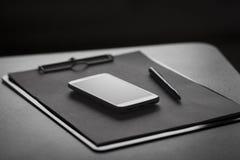 智能手机、剪贴板和笔 免版税库存图片
