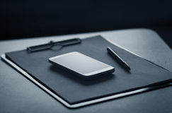 智能手机、剪贴板和笔 免版税库存照片