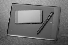 智能手机、图形输入板和铁笔在一张木桌上 一位数字式形象艺术设计师的工作场所细节  艺术背景黑色概念屏蔽油漆红色地点白色 库存图片