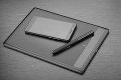 智能手机、数字式图画片剂和铁笔在一张木桌上 一位数字式形象艺术设计师的工作场所细节  库存图片