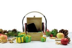 智能手机、耳机和圣诞节闪亮金属片 音乐 现代techn 免版税库存图片