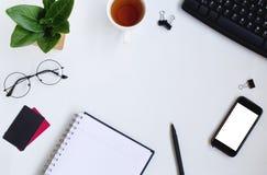 智能手机、键盘、笔记本和信用carrds在白色办公桌上 免版税库存照片