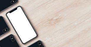 智能手机与copyspace舱内甲板的大模型横幅在木办公桌放置说谎的顶视图 库存图片