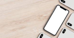 智能手机与copyspace舱内甲板的大模型横幅在木办公桌放置说谎的顶视图 免版税库存照片