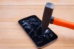 智能手机击中一把锤子 电子修理的概念 特写镜头 库存图片