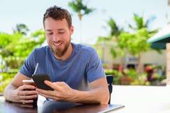 智能手机发短信给饮用的咖啡的人sms在café 免版税库存照片