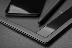智能手机和图形输入板有一支特别象笔一样的铁笔的在一张木桌上 数字式形象艺术de的工作场所细节  库存图片