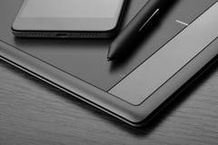 智能手机和数字式图画片剂有一支特别象笔一样的铁笔的在一张木桌上 一张数字式图表的工作场所细节  库存图片