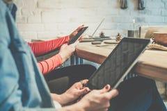 智能手机和数字式片剂特写镜头在女商人的手上坐在木桌上的在咖啡馆 库存照片