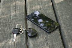 智能手机和汽车钥匙在一张木桌上说谎 库存照片