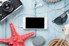 智能手机和照相机在桌上与海星和壳 免版税图库摄影