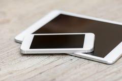 智能手机和片剂在灰色木背景 皇族释放例证