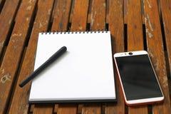 智能手机和笔在木头上把空的笔记本放 免版税库存照片